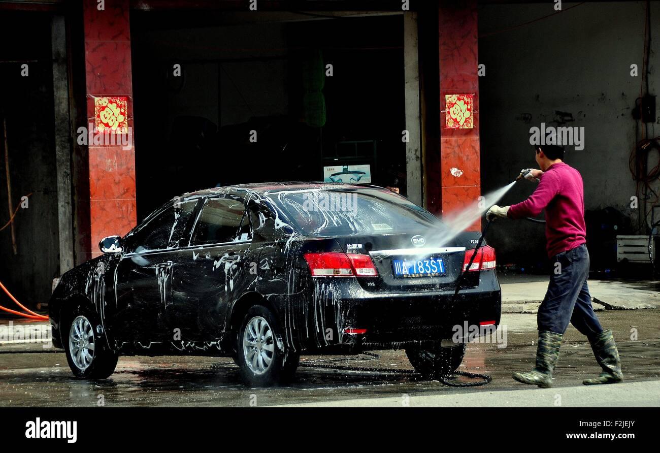 Long Feng, China:  Worker at a local car wash shop hoses suds off a customer's automobile using a high-powered - Stock Image