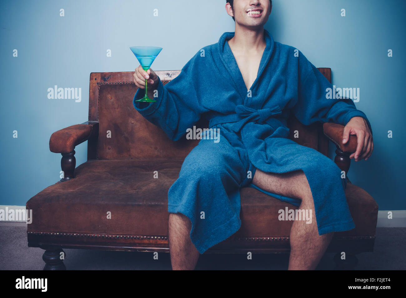 Young man in bathrobe on sofa with cocktail - Stock Image