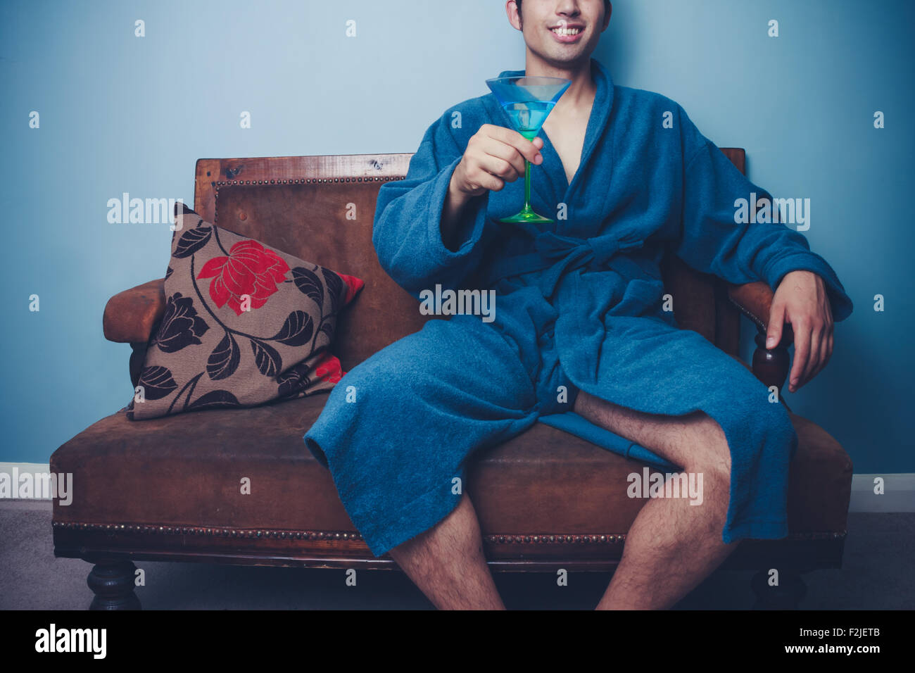 Man in bathrobe with cocktail - Stock Image