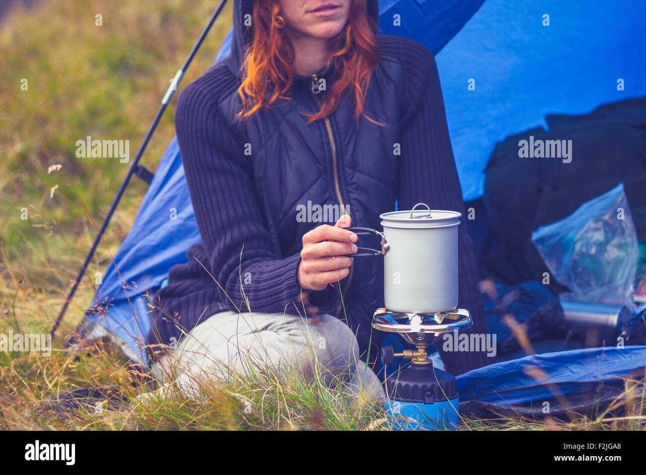 Young woman in tent cooking with camping stove Stock Photo