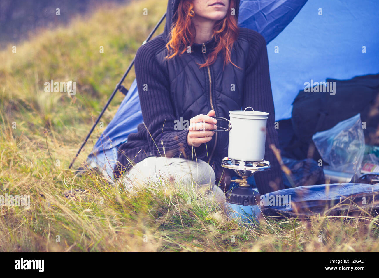 Young woman in tent cooking with camping stove - Stock Image