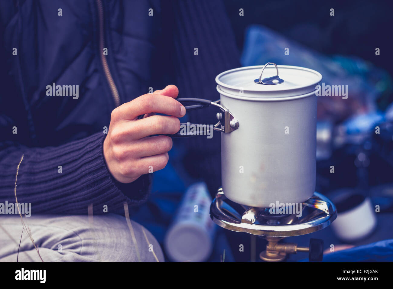 Young woman camping and cooking with stove - Stock Image