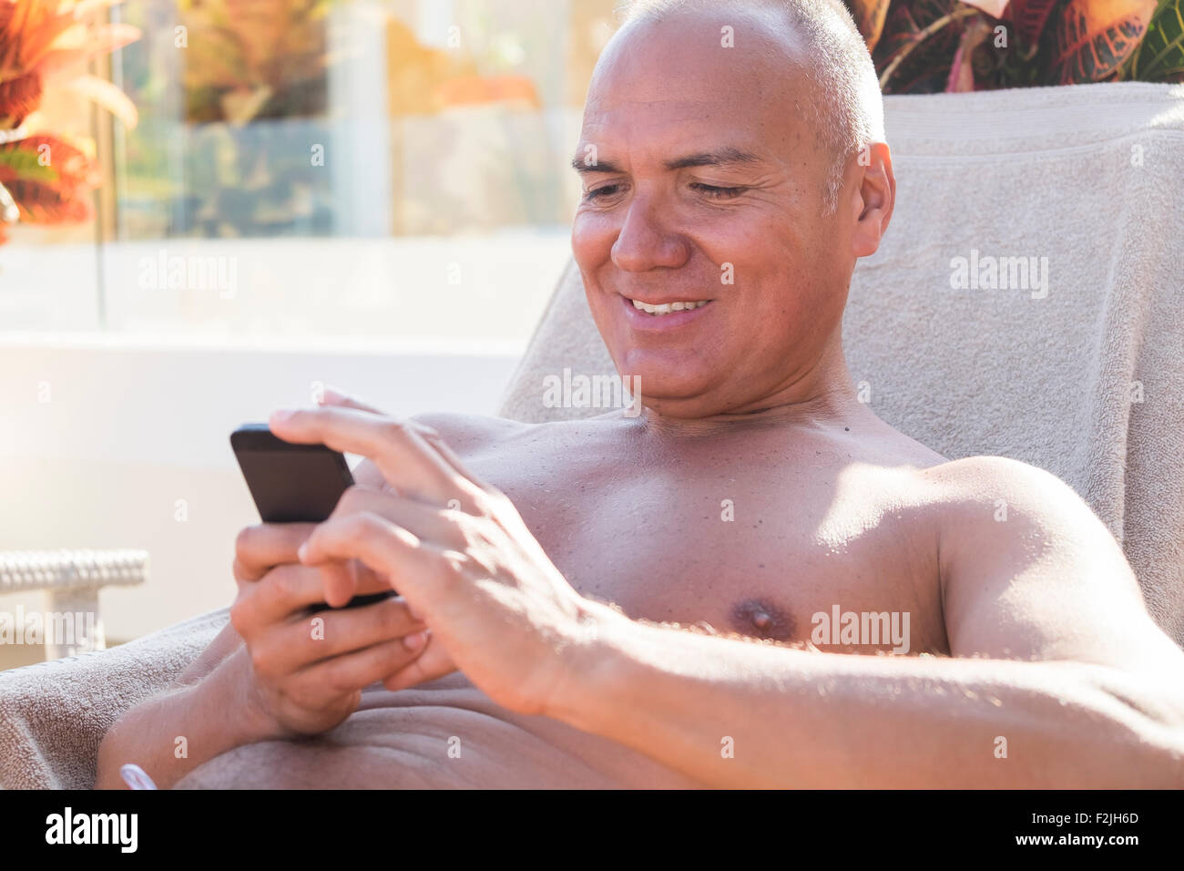 Smiling holidaymaker looking at his smartphone - Stock Image