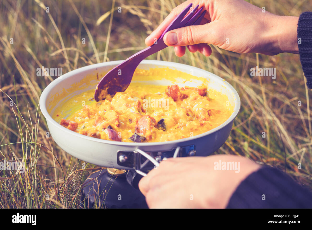Hands of woman cooking egg outside on camping stove - Stock Image