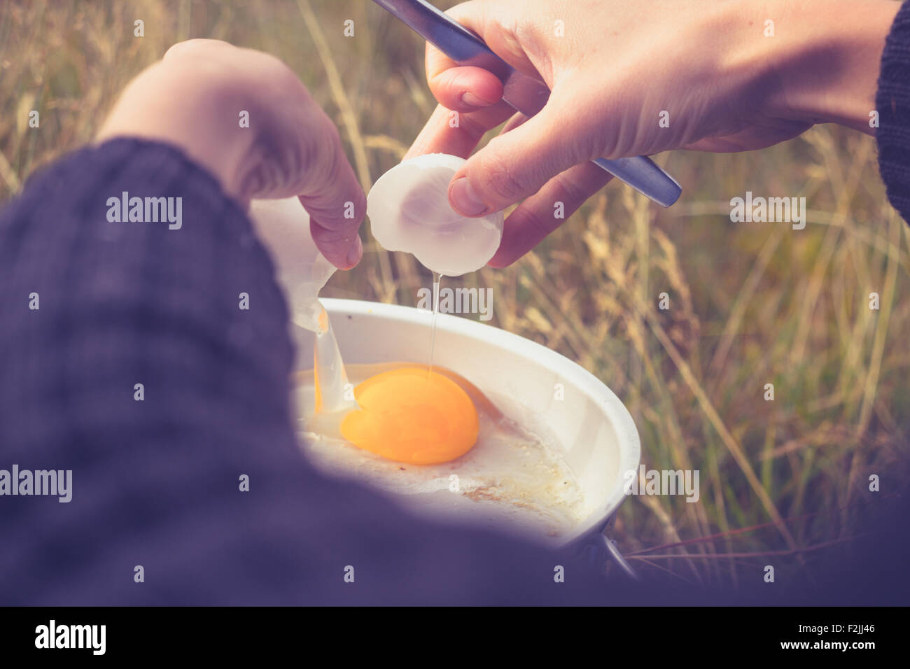 Hands of young woman cooking egg in nature Stock Photo