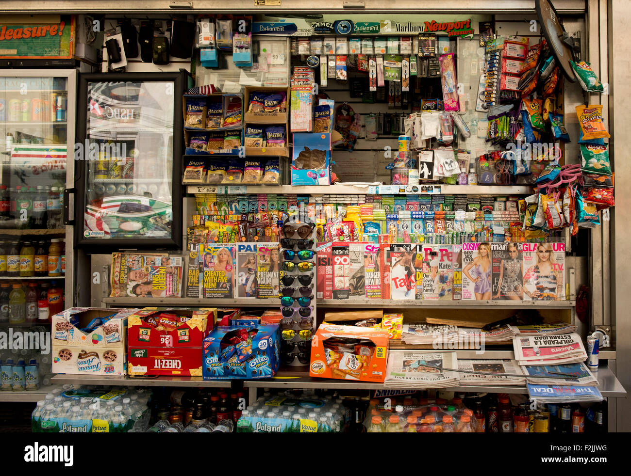 A cluttered Manhattan newsstand selling newspapers, magazines, snacks, sodas, sunglasses and cigarettes;  New York - Stock Image