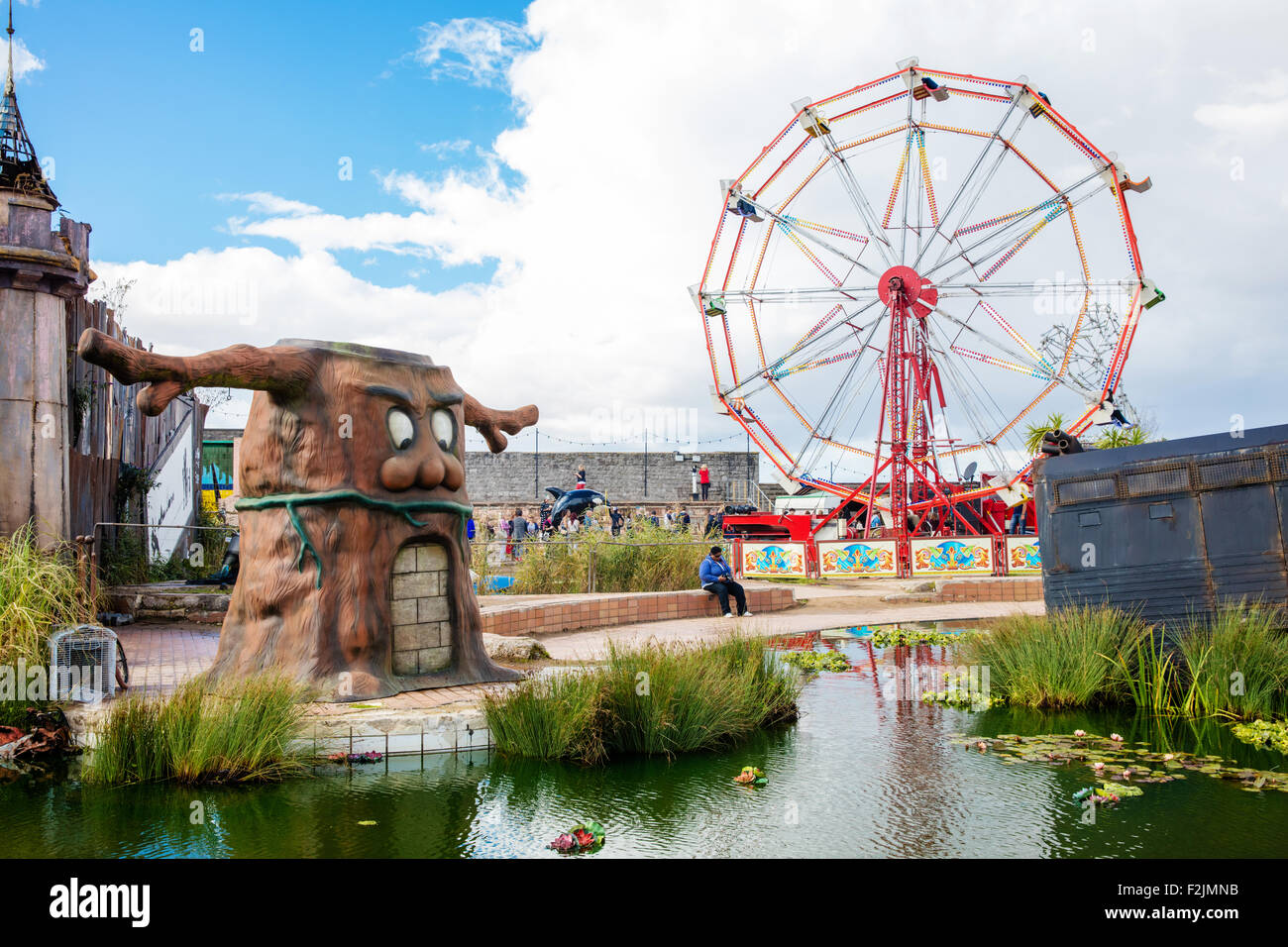 View across the lake at Banksy's Dismaland in Weston super Mare with bricked up Play tree and empty ferris wheel - Stock Image