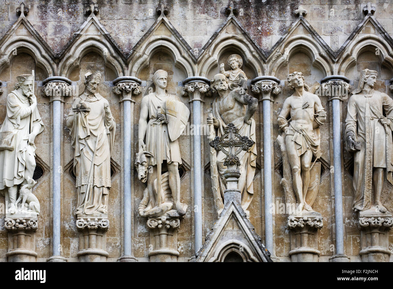 Stone sculptures of Christian saints and martyrs above the entrance to Salisbury cathedral Wiltshire UK - Stock Image