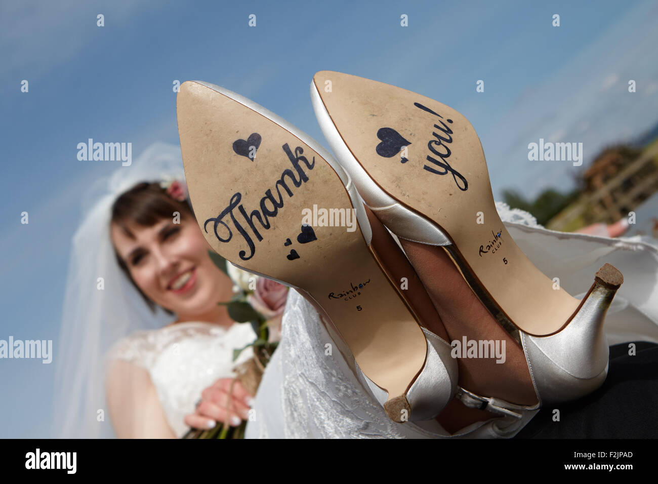 Bride with thank you written on shoes - Stock Image