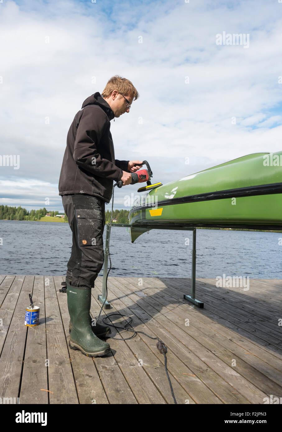 Man polishing a canoe - Stock Image