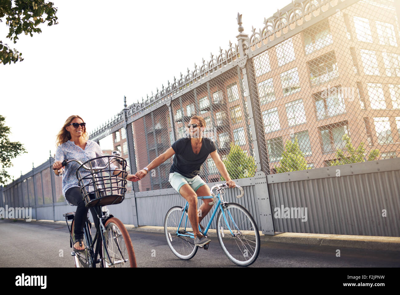 Romantic couple holding hands as they go cycling riding their bikes down an urban street past apartment blocks - Stock Image