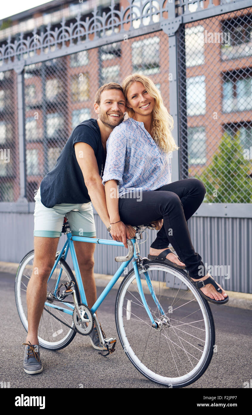 Loving couple riding bikes, woman on handlebar - Stock Image