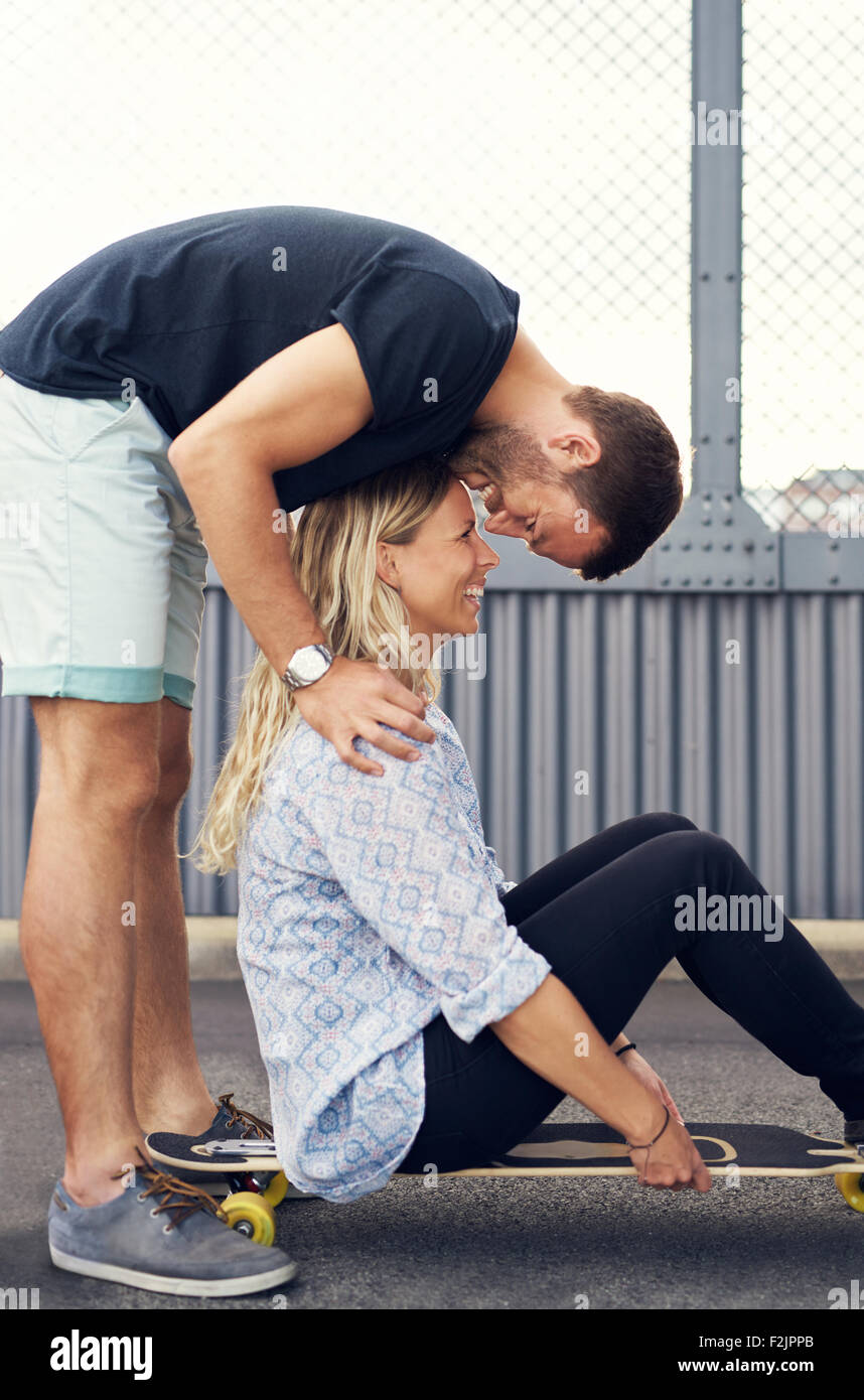 Man leaning over woman kissing her while she smiles - Stock Image