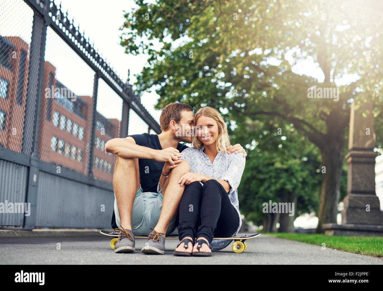 Man caressing woman in a charming way, big city couple - Stock Image