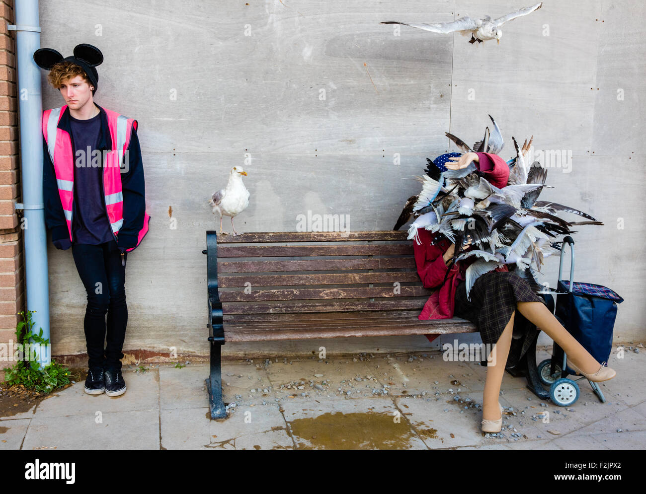Desultory mouse eared staff next to Banksy's ' Woman Attacked by Seagulls ' sculpture at Dismaland in - Stock Image