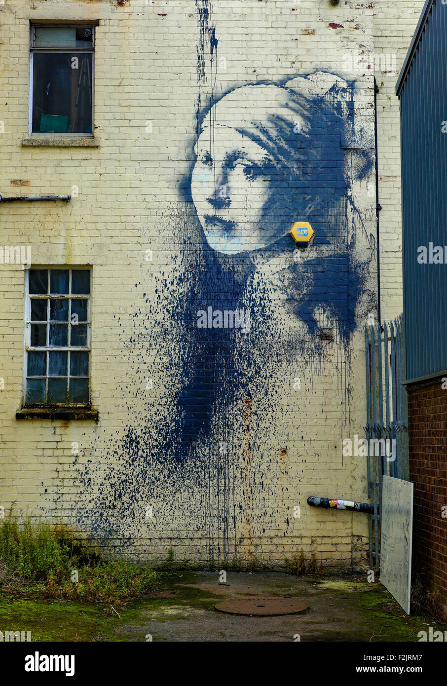 Banksy's Girl with a Pierced Eardrum graffitti on a building by Bristol's floating harbour - Stock Image