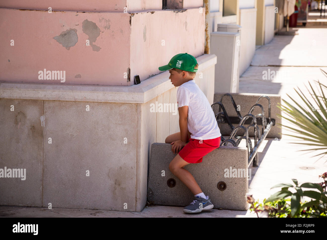 Young boy watching mobile phone screen in shade of building in Lecce italy Stock Photo