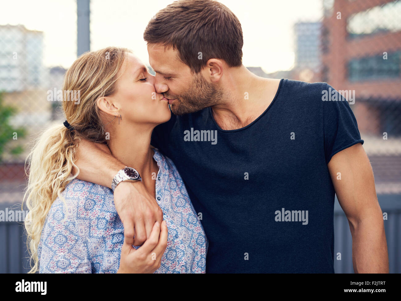 Amorous attractive young couple enjoy a romantic kiss as they stand arm in arm outdoors in an urban street - Stock Image