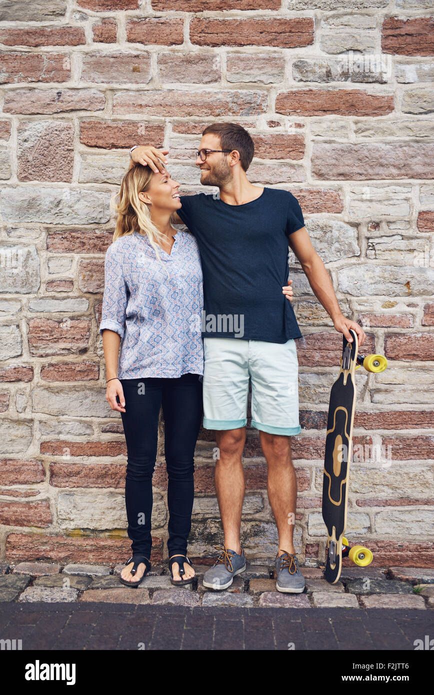 Humorous couple loving each other standing against wall - Stock Image
