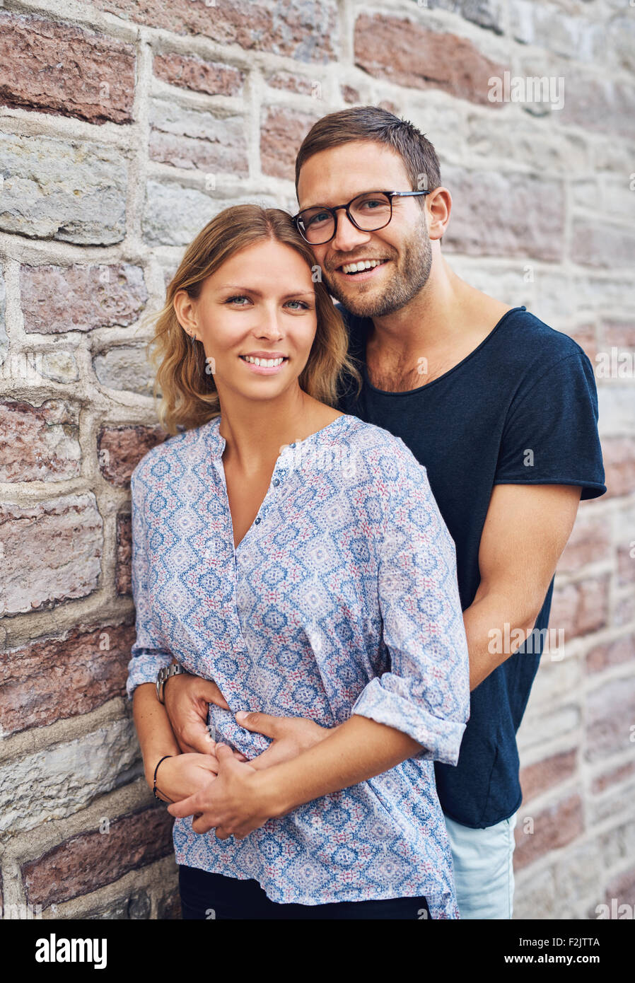 Half Body Shot of a Sweet Man Hugging his Girlfriend From her Behind While Leaning Against Concrete Wall and Smiles - Stock Image