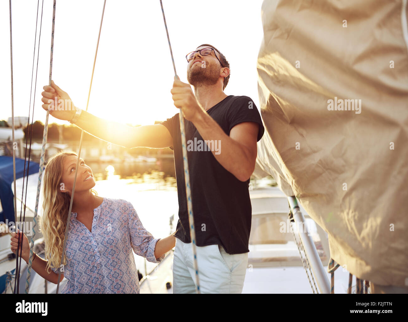 Couple on Their Sail Boat Checking it Before heading out - Stock Image