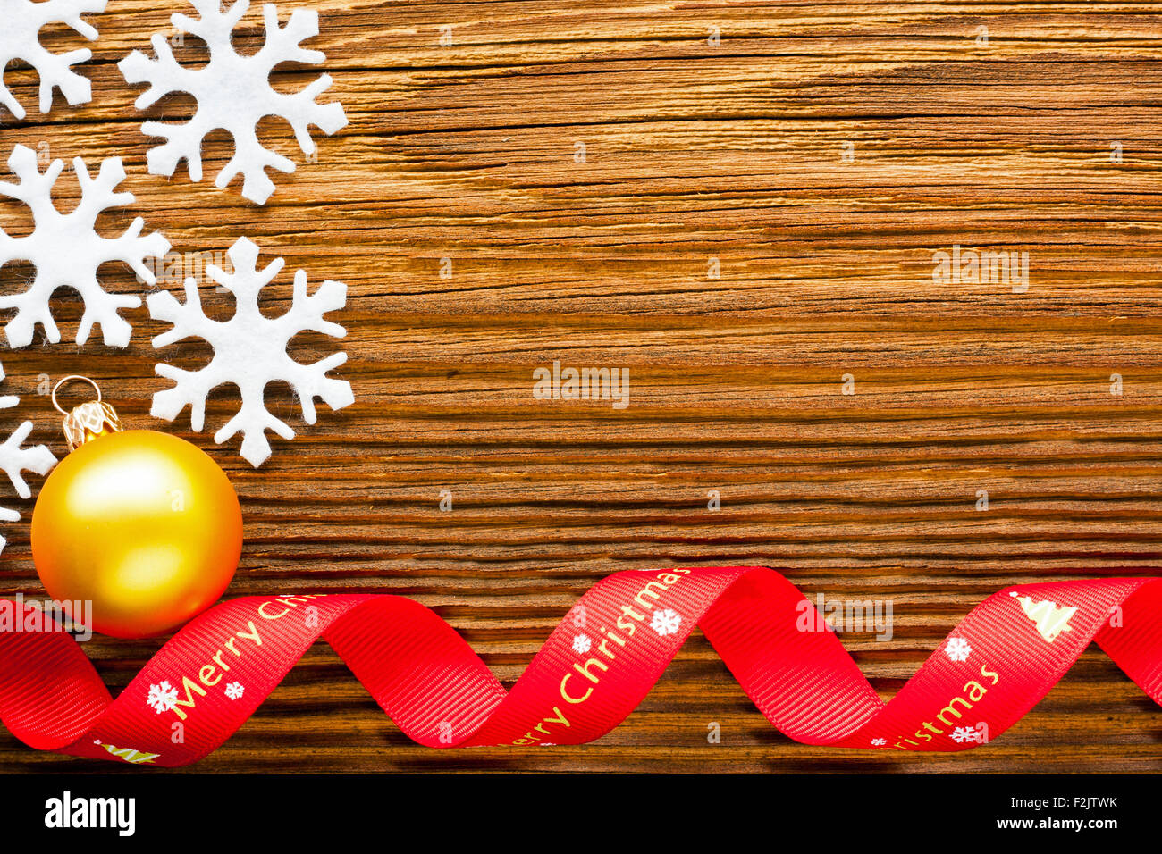 Christmas background - snowflakes and red ribbon on wooden table - Stock Image