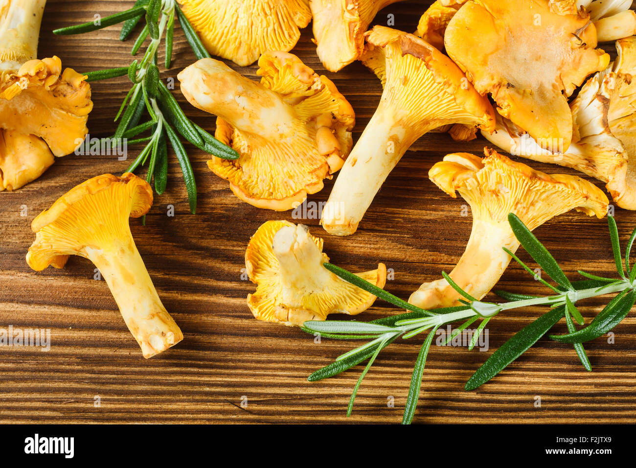 Yellow chanterelles on wooden table - Stock Image