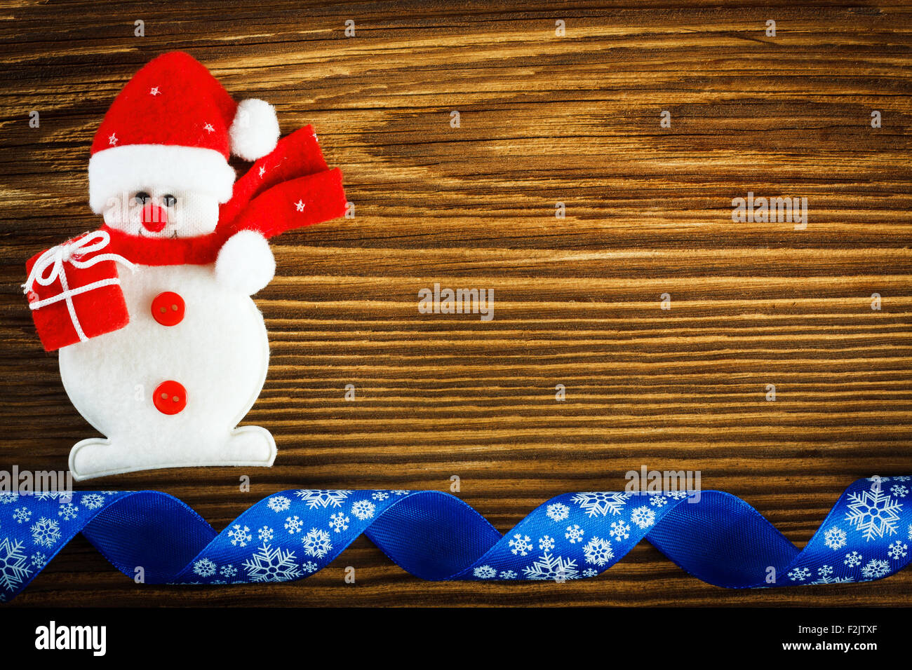 Christmas background - snowman and blue ribbon on wooden table - Stock Image