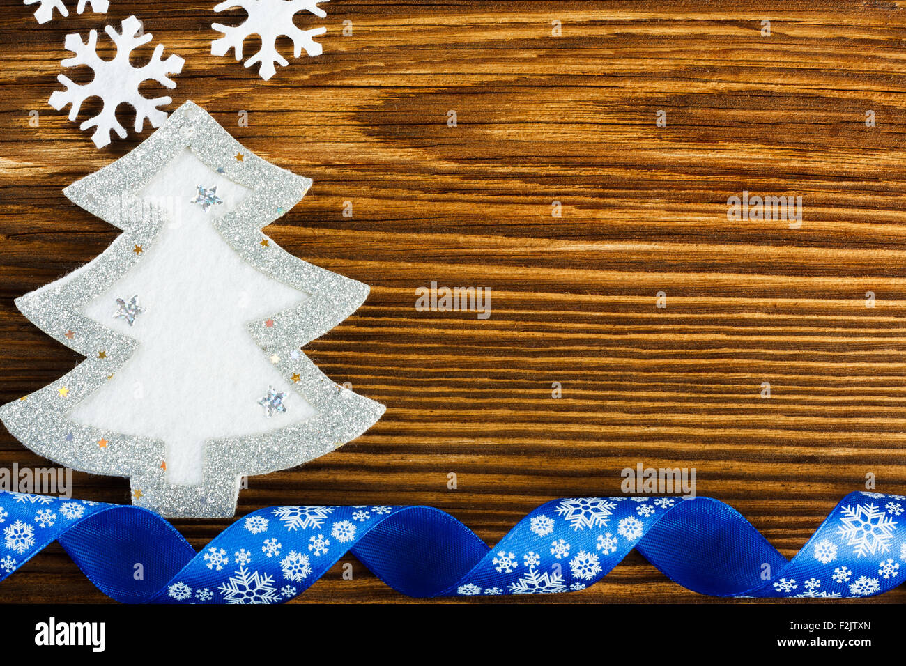 Christmas background - snowflakes, christmas tree and blue ribbon on wooden table - Stock Image