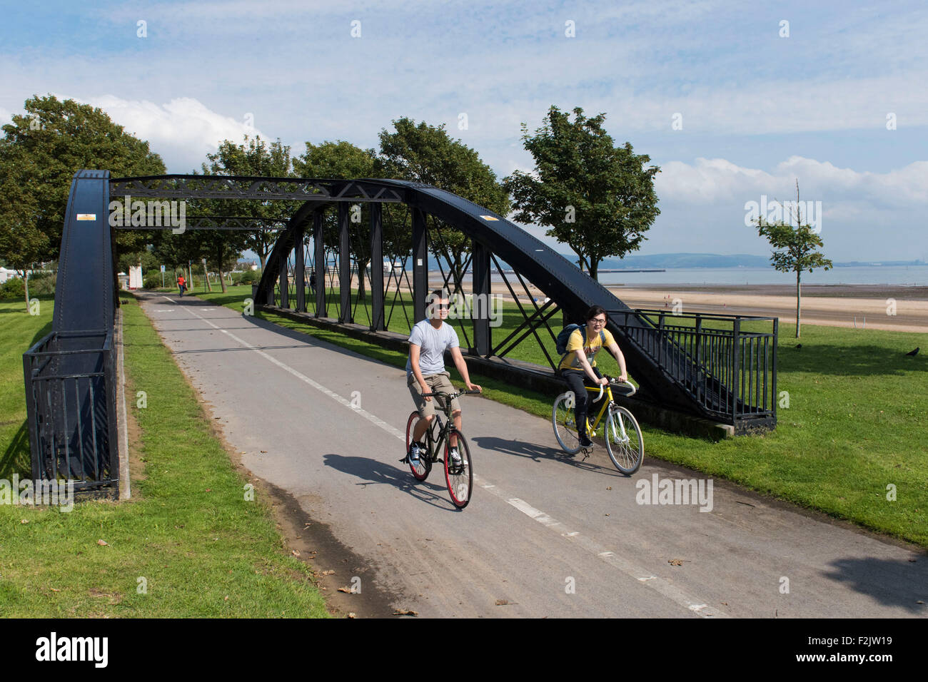 Cyclists cycle in a cycle lane along the Swansea beach promenade in Swansea, South Wales. - Stock Image