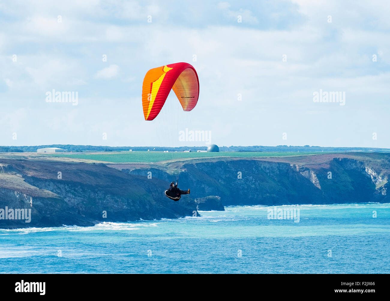 a paraglider gliding over the sea at st.agnes head on the coast of cornwall, england, uk - Stock Image