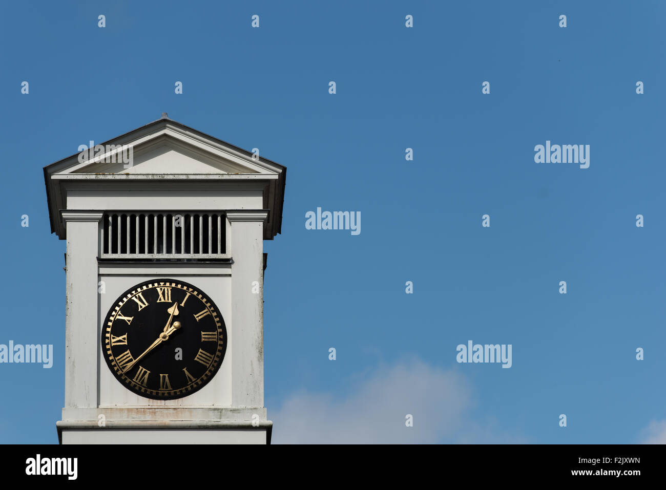 a roman numeral clock tower with a blue sky and white cloud background - Stock Image