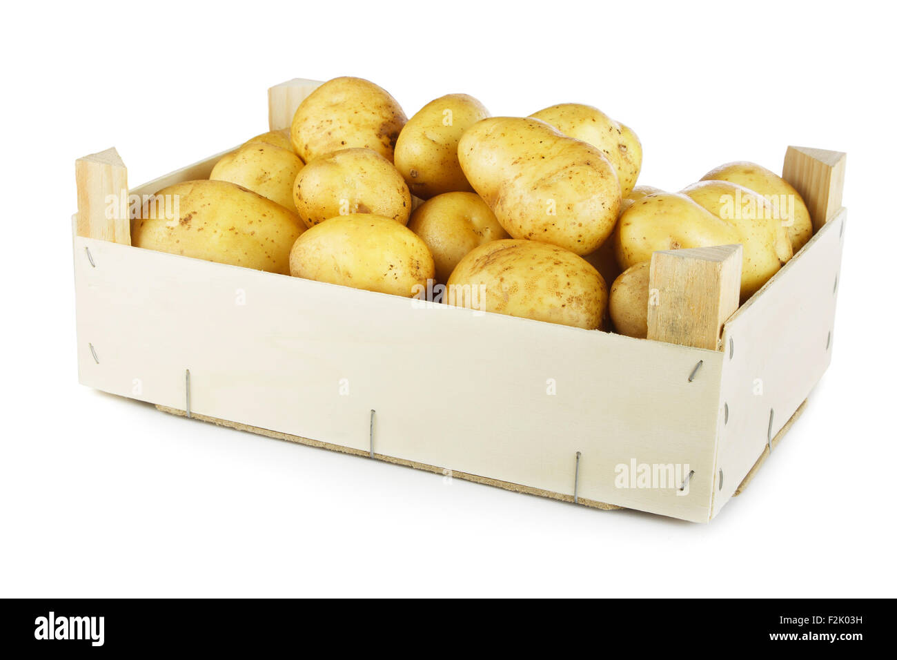 Potatoes in wooden box isolated on white background - Stock Image