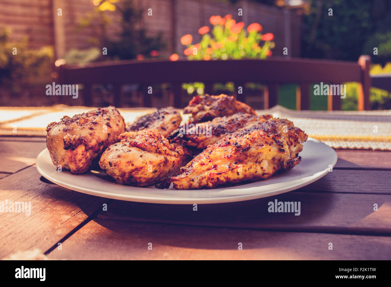 Chicken on a plate outside - Stock Image