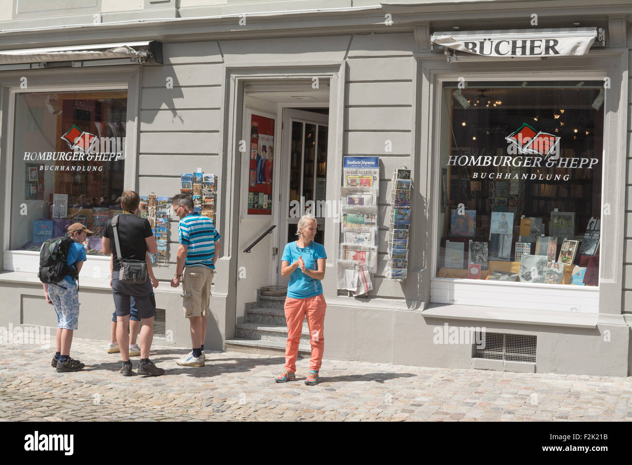people selecting postcards outside Homburger & Hepp bookstore, Cathedral Square, Konstanz, Germany, Europe - Stock Image