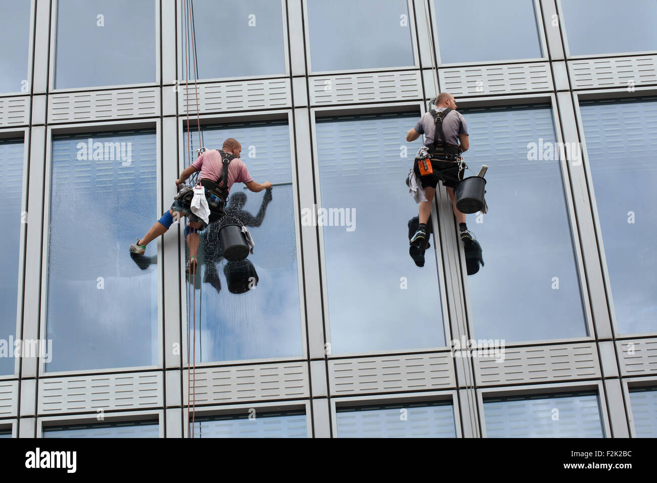 Two rope access workers  (rope cleaners) clean windows in an office building in Charles Square in Prague, Czech - Stock Image
