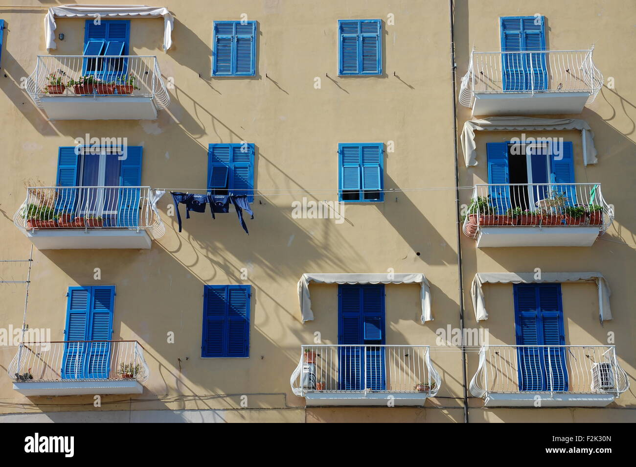 Blue shutters and white balconies on the facade of a house in the town of Porto Santo Stefano, Italy. - Stock Image