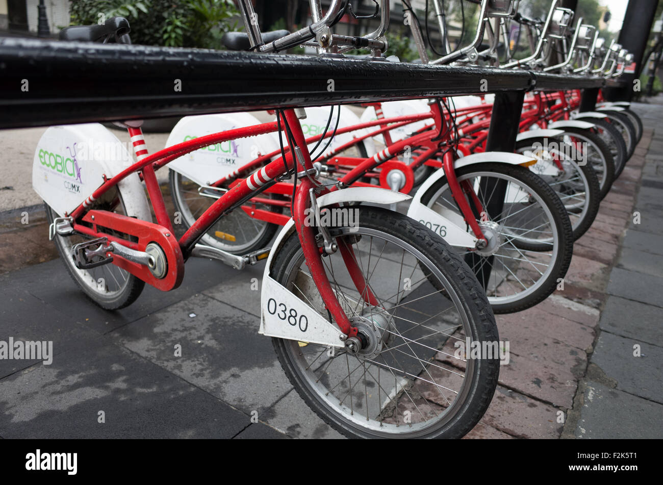 Red bikes on a bikesharing rack in Mexico City, Mexico. - Stock Image