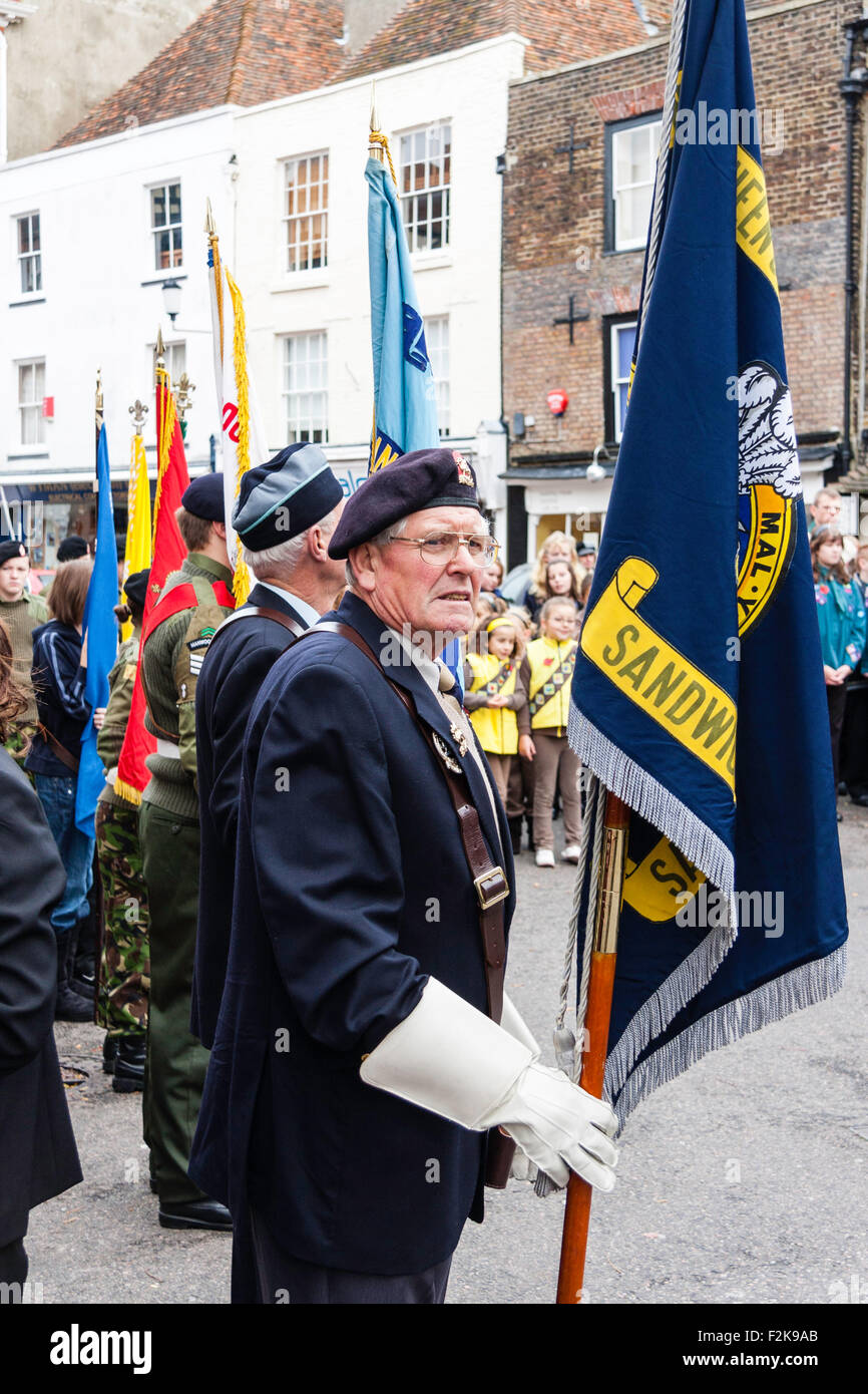 England, Sandwich. Remembrance Sunday. Ex-serviceman standing holding regimental flag during ceremony in town square - Stock Image