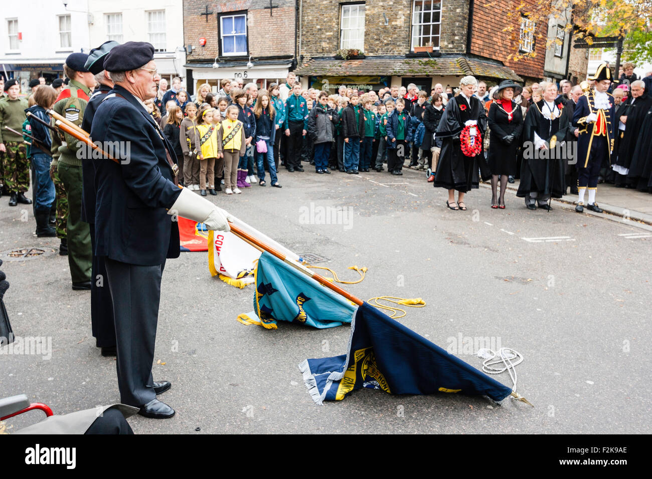 England, Sandwich. Remembrance Sunday. Ex-servicemen standing lowering regimental flags during silence in town square - Stock Image