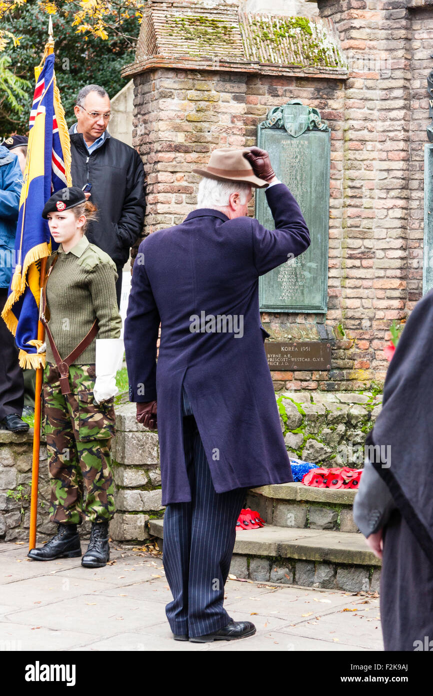 England, Sandwich. Remembrance Sunday. Senior man tipping hat at the war memorial after laying wreath of poppies. Stock Photo
