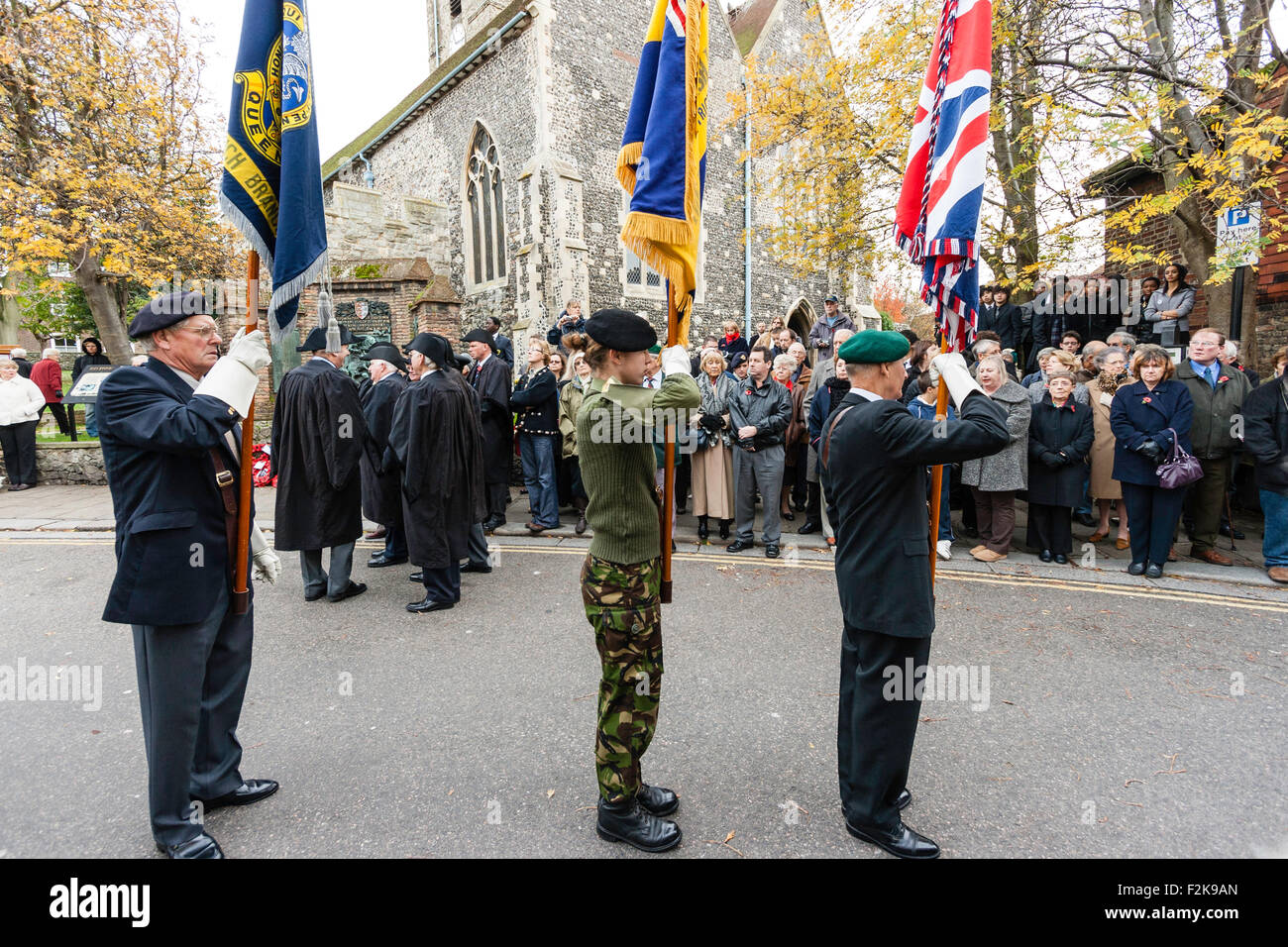 Remembrance Sunday in November. Ex-servicemen and serving soldiers standing at attention while holding flags during - Stock Image