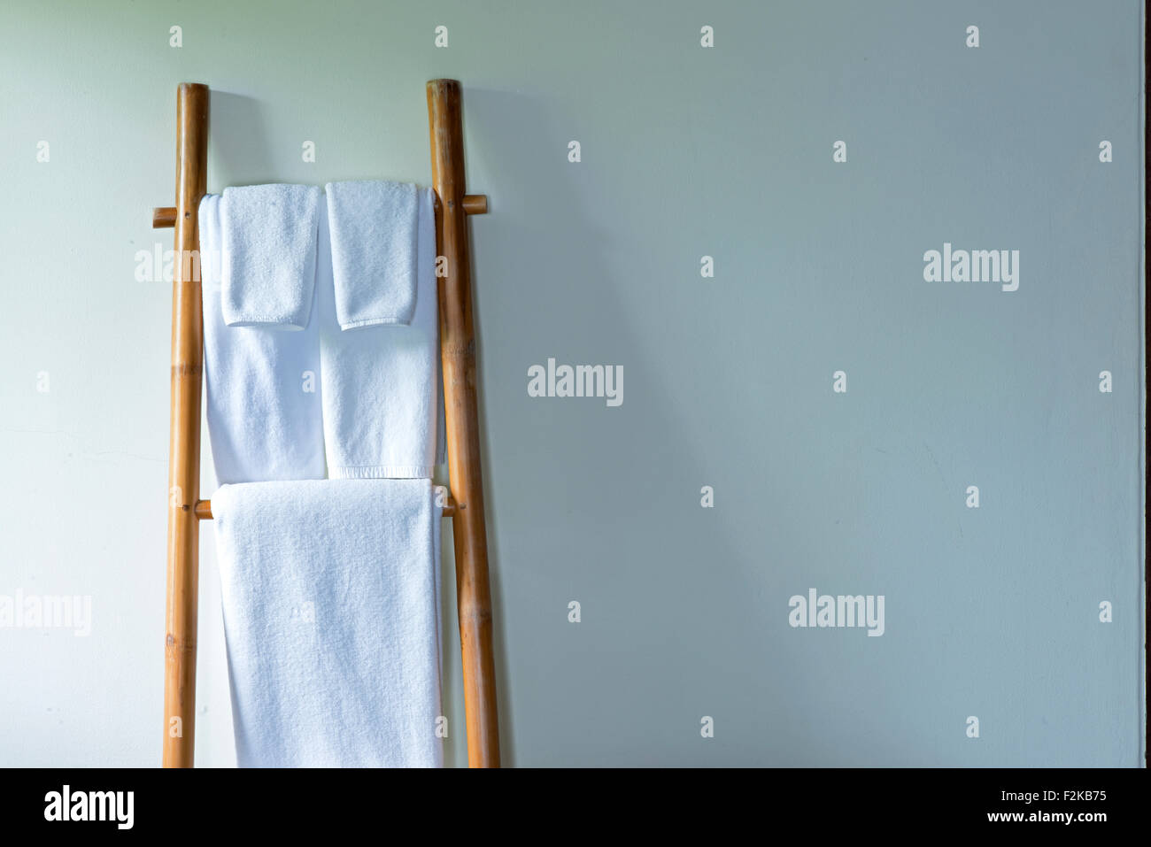 Towels hanging on the bamboo hanger and ready to use - Stock Image