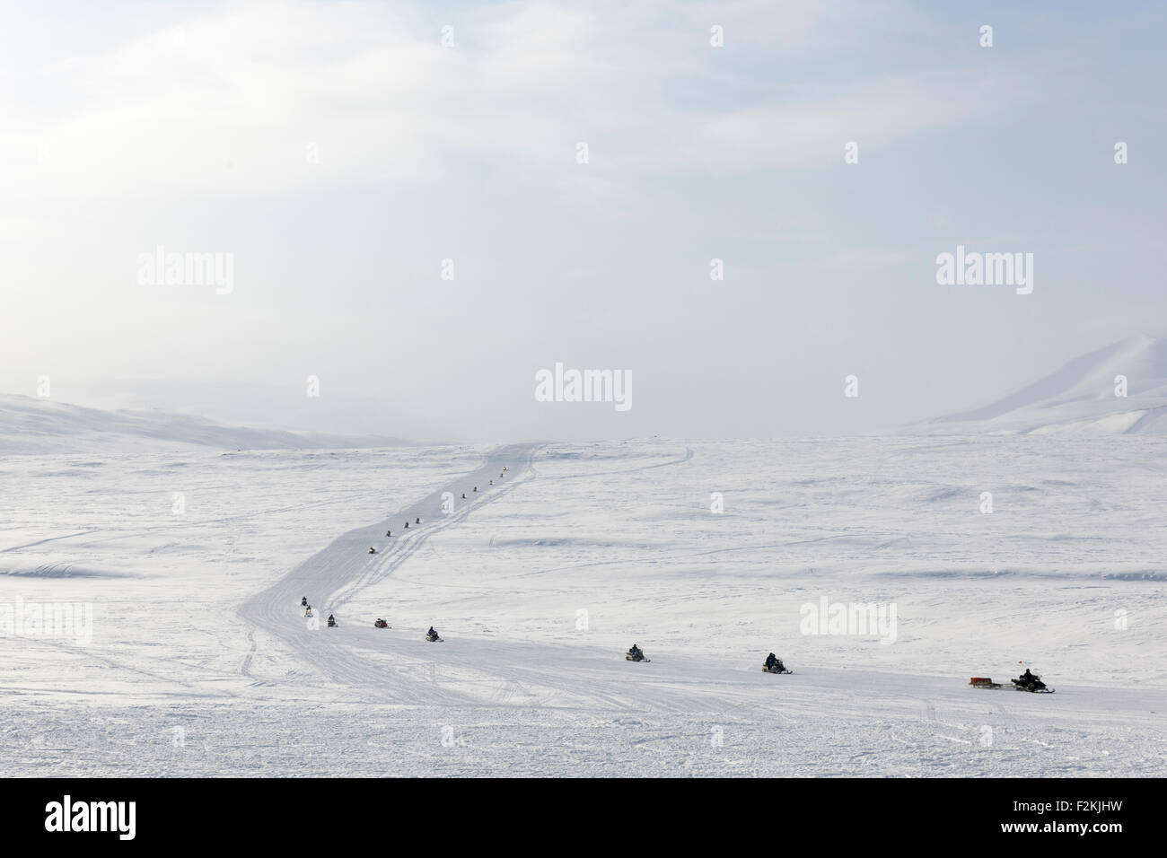 Group of snowmobiling people on the way at Arctic Spitsbergen, Colesdalen, Svalbard, Norway. - Stock Image