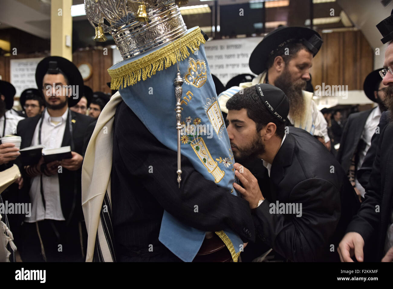 A religious Jewish man kisses the Torah as it is returned to the Holy Ark during morning synagogue services in Brooklyn, Stock Photo