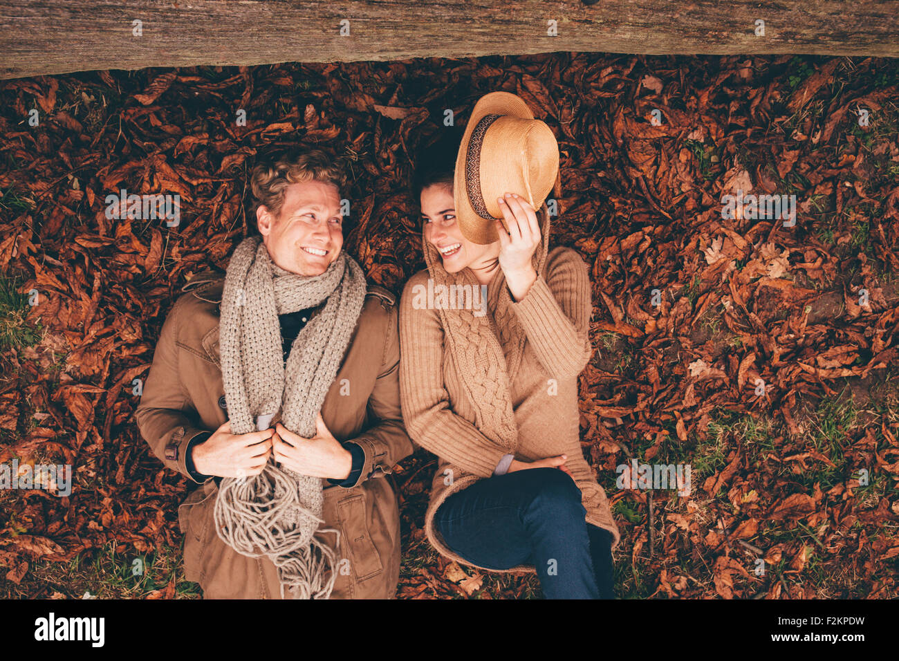 Young couple lying side by side on autumn leaves in an park - Stock Image