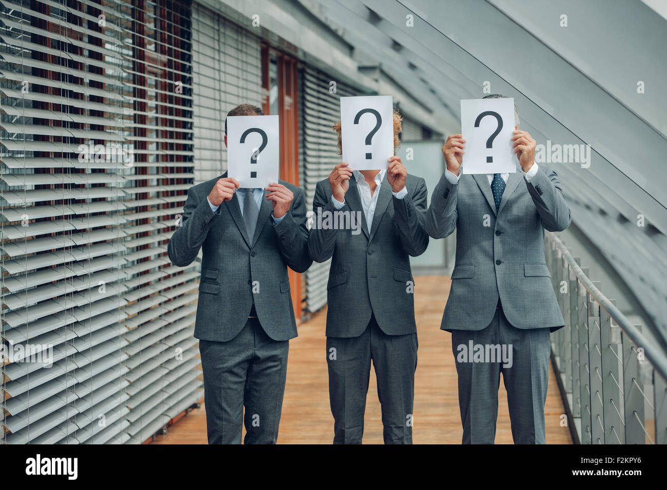 Business people with question mark on placards - Stock Image