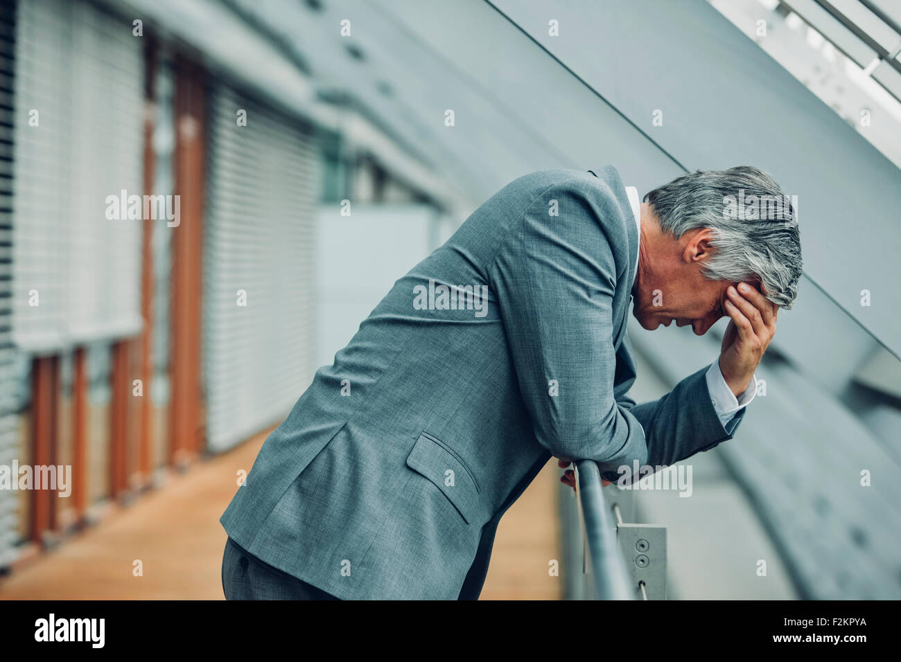 Desperate businessman leaning on railing - Stock Image