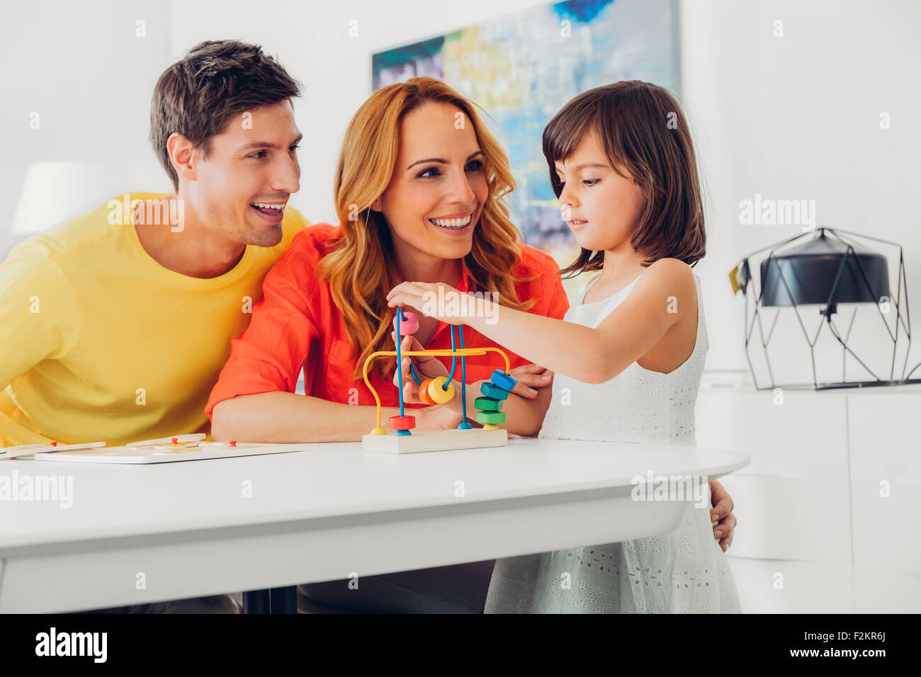 Parents with daughter playing with toy on table at home - Stock Image