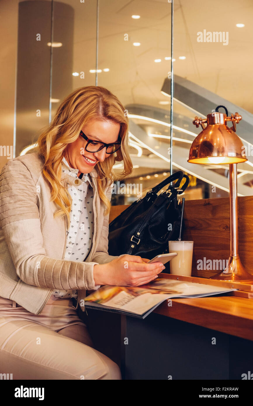Blond woman sitting in a coffee shop reading text message on her smartphone - Stock Image